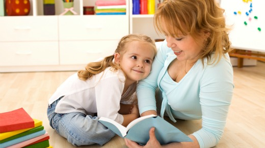Woman reading to her little girl, sitting on the floor